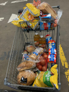 cart full of groceries in a parking lot